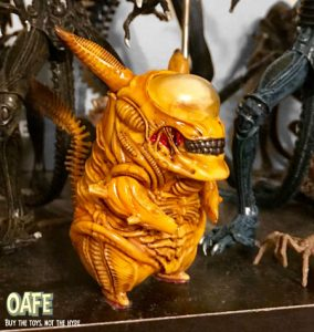 a short, yellow Xenomorph with large pointy ears
