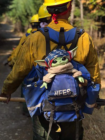 a firefighter carries Baby Yoday through the woods in a backpack