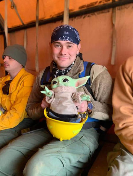 a firefighter rests with Baby Yoda sitting in his helmet