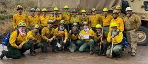 the team of firefighters pose with their tools and Baby Yoda