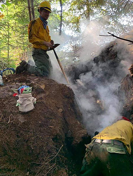 Baby Yoda in the woods with firefighters as they dig a fire break