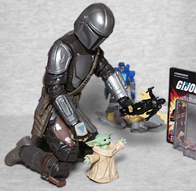The Mandalorian helps baby Yoda play with the World's Smallest Snake-Eyes