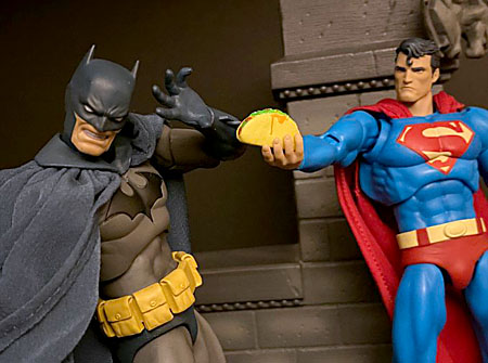 Superman holds out a taco to Batman, who recoils in horror