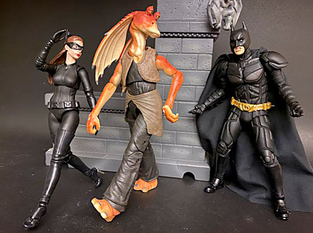 Catwoman walks hand in hand with a smug Jar Jar Binks, while Batman seethes angrily watching them leave